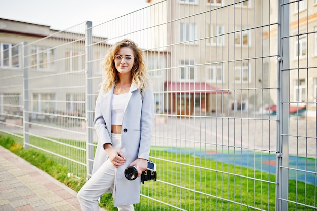 Stylish curly blonde model girl wear on white posing against fence.
