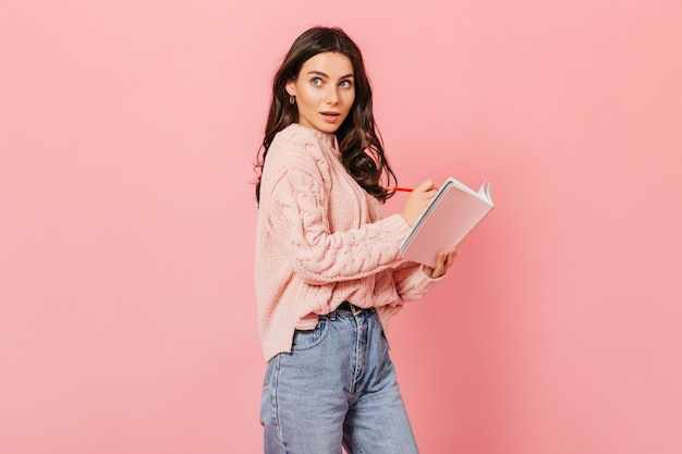 Stylish curly brunette woman posing with notebook and red pen on pink background.