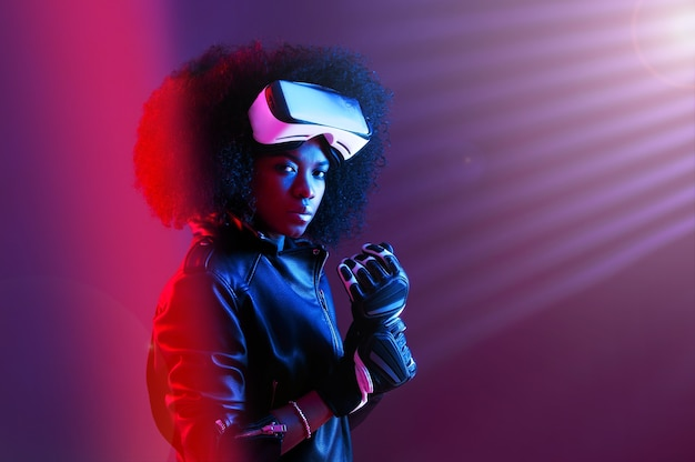 Stylish curly dark haired girl dressed in black leather jacket and gloves is wearing the virtual reality glasses on her head in the dark studio with neon light