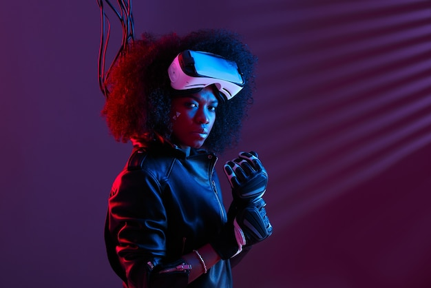 黒革のジャケットと手袋を身に着けたスタイリッシュな巻き毛の暗い髪の少女は、ネオンライトのある暗いスタジオで彼女の頭にバーチャルリアリティグラスを着ています。サイバーパンクキャラクター