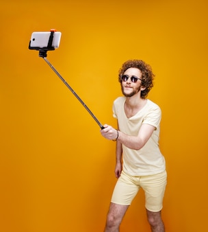 Stylish curly-haired man taking selfie with monopod