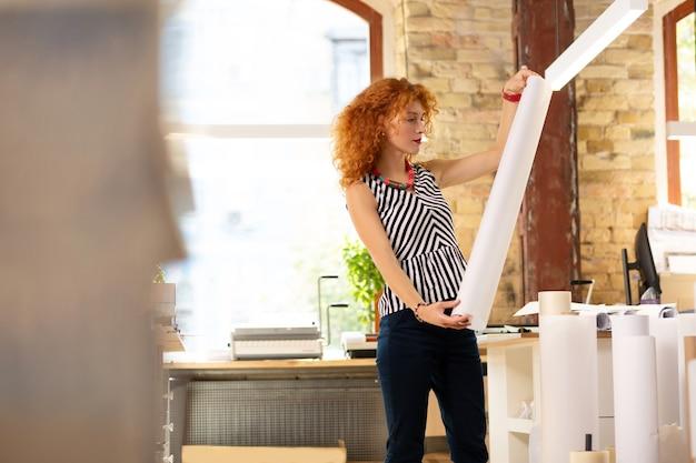 スタイリッシュな巻き毛の女性。紙のロールを保持しながらストライプのブラウスを着て出版社で働くスタイリッシュな巻き毛の女性