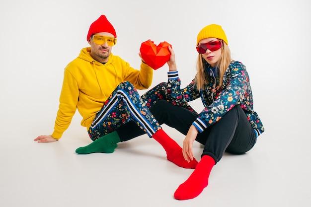 Стильная милая пара мужчина и женщина в красочной одежде держит сердце на белом фоне