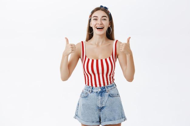 Elegante ragazza pon pon femminile carina ed entusiasta in top a strisce pin-up e fascia alzando i pollici in su