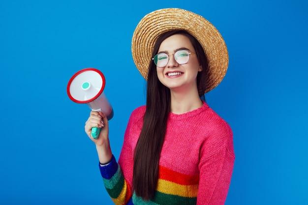 Стильная милая девушка в радужном свитере говорит в мегафон и улыбается