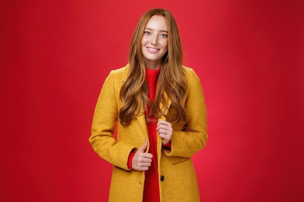 Elegante e carina bella donna rossa in cappotto giallo sulla strada per il lavoro, afferrando l'ordine per fare il caffè con un simpatico sorriso amichevole che tocca il pulsante e posa su sfondo rosso.
