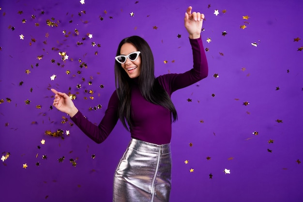 Stylish cute  woman dancing in falling confetti attending night club isolated vibrant color purple wall