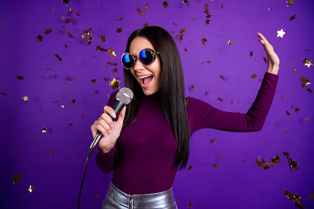 Stylish cute woman in eye wear glasses singing into microphone performing her new song isolated vibrant purple color wall