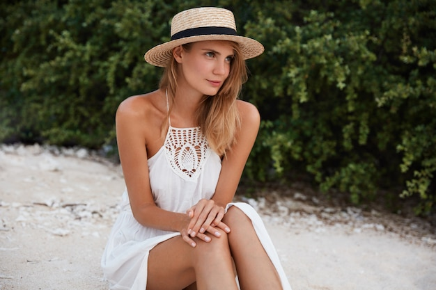 Stylish cute young woman in hat and dress has dreamy expression as sits on ground, thinks or contemplates about something, enjoys leisure during summer holidays. lifestyle, recreation concept