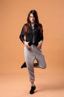 Стильная темноволосая девушка в белой рубашке, серых брюках, черной куртке и черных кроссовках позирует на бежевом фоне в студии.
