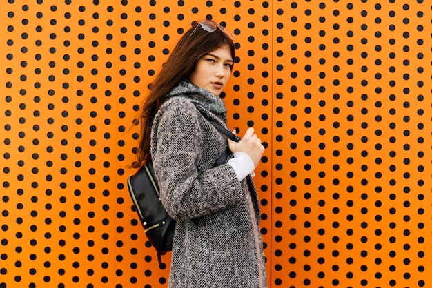 Стильная темноволосая девушка в сером пальто позирует на оранжевой необычной стене, мода, с рюкзаком