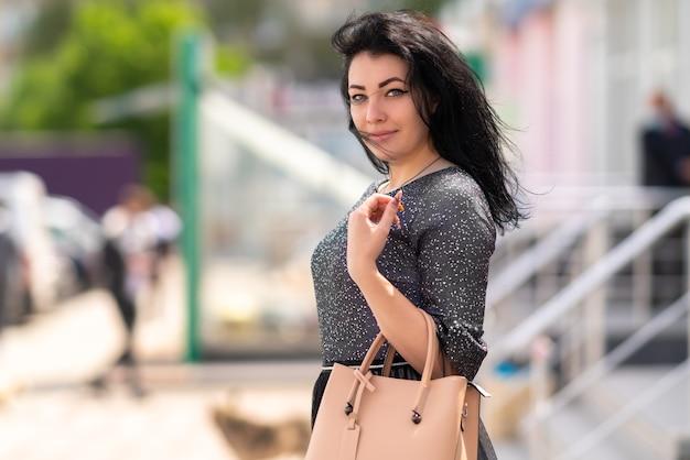 Стильная темноволосая женщина гуляет по городу с кожаной сумочкой