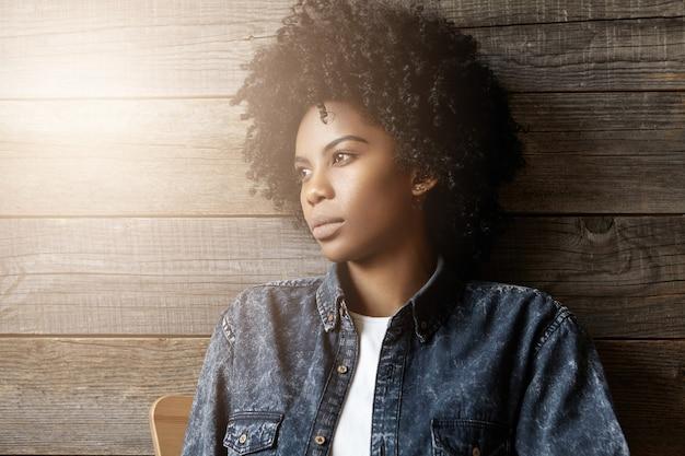 屋内で休息するトレンディなジーンズのジャケットに身を包んだアフロの髪型のスタイリッシュな浅黒い肌の少女