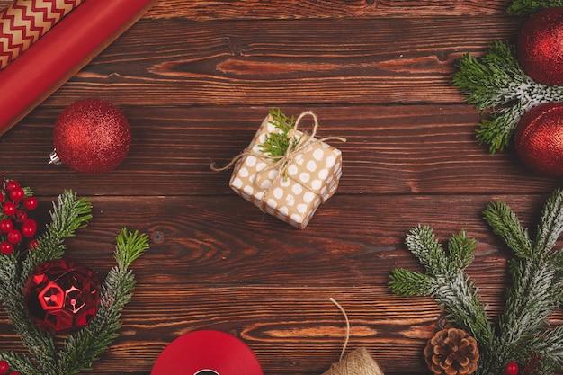 Стильный оформленный рождественский подарок с лентой на деревянном фоне, вид сверху