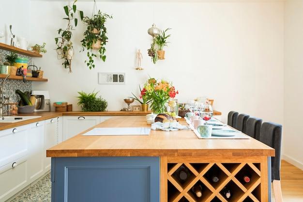 ダイニングテーブル、椅子、食器、その他のキッチンアクセサリーを備えたキッチンスペースインテリアのスタイリッシュなデザイン。地中海スタイル。明るく日当たりの良い空間。明るい色。夏の雰囲気。