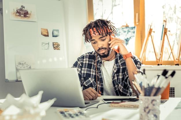 スタイリッシュなデザイナー。電話で話す四角いシャツと赤いヘッドバンドを身に着けているスタイリッシュなインテリアデザイナー