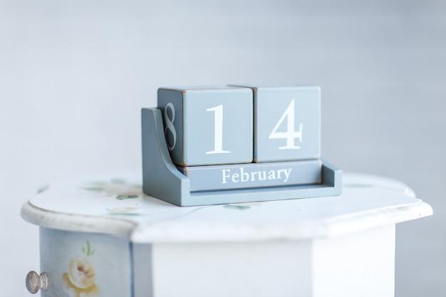 ベッドサイドテーブルに2月14日の言葉が書かれたスタイリッシュな卓上カレンダー。