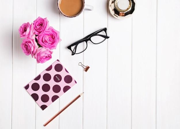 スタイリッシュなデスク。白い背景の上のコーヒー、花、メガネ、その他のアクセサリー