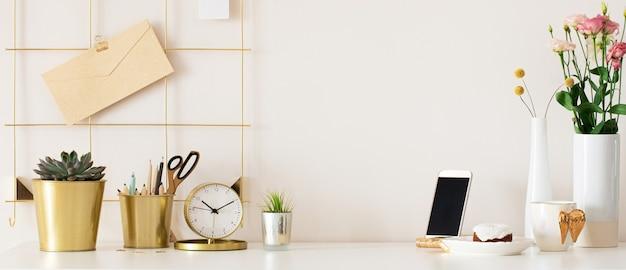 식물과 잎이 있는 흰색 테이블 배경이 있는 세련된 책상 인테리어. 현대 홈 오피스 인테리어 파노라마 배너 배경