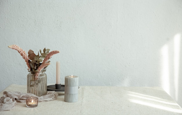Stylish details of the interior decor against the background of a white wall with sunbeams.