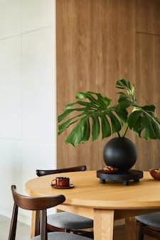 식탁, 의자 및 개인 액세서리가 있는 세련된 식당 인테리어 디자인. 창의적인 벽, 흰색 및 나무 패널. 최소한의 스타일 식물 사랑 개념입니다.
