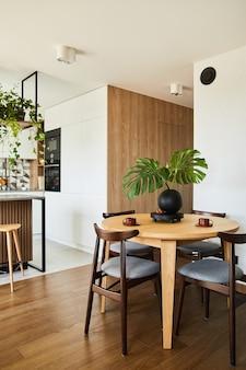 식탁이 있는 세련된 식당 인테리어 디자인. 배경에 주방 액세서리가 있는 작업 공간. 창의적인 벽, 흰색 및 나무 패널. 최소한의 스타일 식물 사랑 개념입니다.