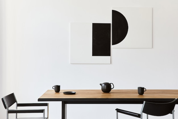 디자인 목재 패밀리 테이블, 검은 색 의자, 머그잔이 달린 주전자, 벽에 걸린 예술 그림 및 현대 가정 장식의 우아한 액세서리가있는 세련된 식당 인테리어 ..