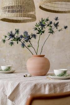 Стильный интерьер столовой с обеденным столом, дизайнерским креслом, подвесными светильниками из ротанга, чашками кофе, букетом сухоцветов в вазе и элегантным декором. гранж стена. шаблон.