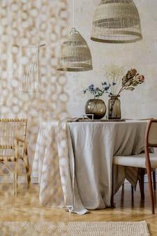 Стильный интерьер столовой с деревянным столом, дизайнерскими стульями, подвесным светильником из ротанга, весенними цветами в вазе, красивыми тарелками, растениями и элегантным декором. концепция ваби-саби ..