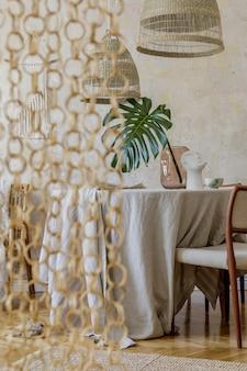 木製のテーブル、デザインチェア、籐のペンダントランプ、花瓶のトロピカルリーフ、美しいプレート、エレガントな装飾が施されたスタイリッシュなダイニングルームのインテリア。わびさびのコンセプト。レンプレート。