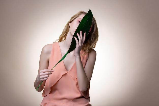 スタイリッシュなドレス。大きな緑の葉を持ったスタイリッシュなドレスを着た優しい魅力的なブロンドの髪のモデル