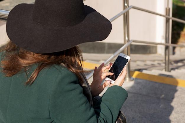 Стильная одетая молодая женщина набирает смс на мобильном телефоне с разбитым экраном