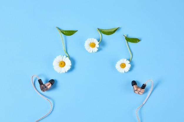 青の背景にノートの形でスタイリッシュなイヤホンとカモミールの花
