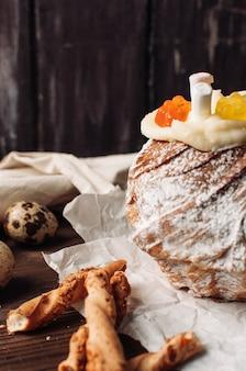卵とグリッシーニと羊皮紙の紙にマシュマロとゼリーのクマとスタイリッシュなイースターケーキ