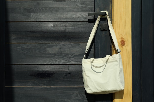 Stylish eco bag hanging on the doorknob, space for text
