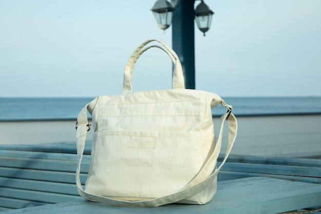 Stylish eco bag outdoor on wooden counter against sea horizon