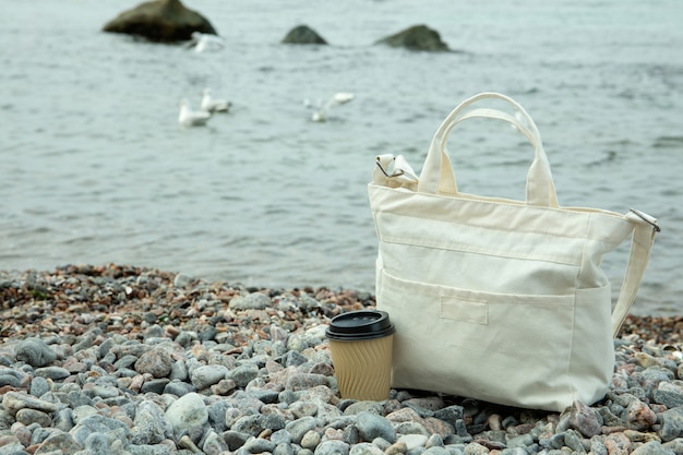 Stylish eco bag and paper cup outdoor on sea shore