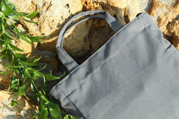 Stylish eco bag and twig lies on stone outdoor