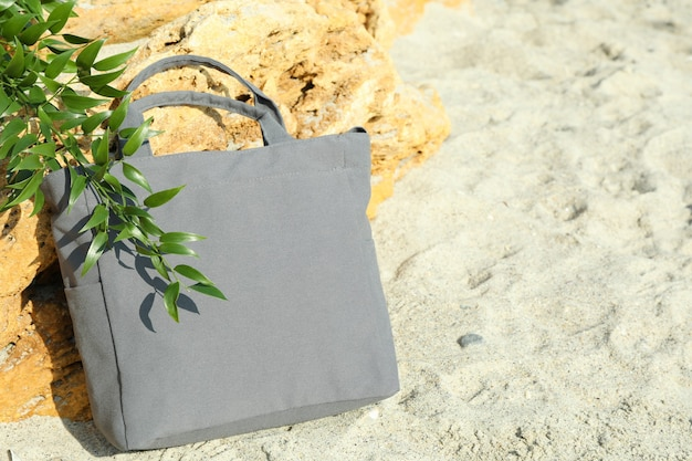 Stylish eco bag and twig outdoor on beach, space for text