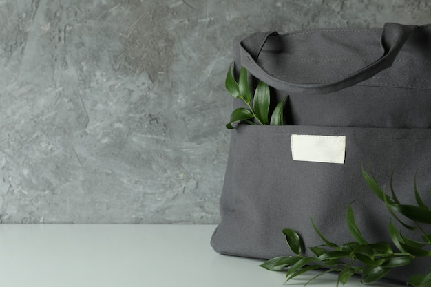 Stylish eco bag with branches against gray textured background