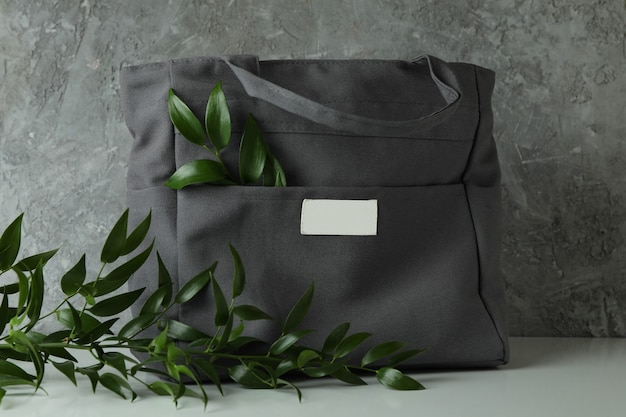 Stylish eco bag with branches against gray textured surface