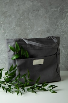 Stylish eco bag with branches against gray textured