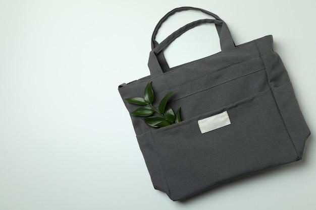 Stylish eco bag with twig on white background