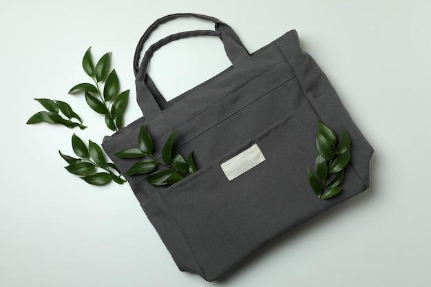 Stylish eco bag with twigs on white background