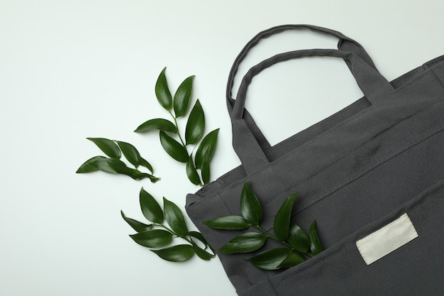 Stylish eco bag with twigs on white