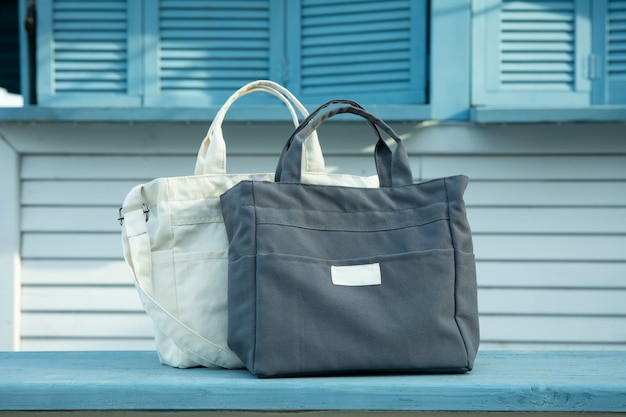 Stylish eco bags outdoor on wooden counter