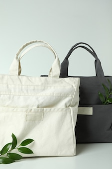 Stylish eco bags and twigs on white background