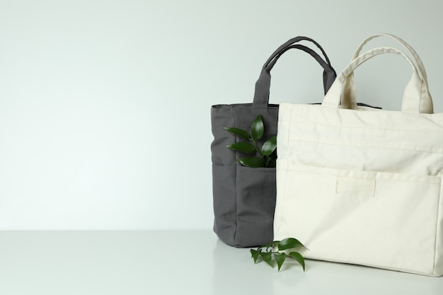 Stylish eco bags and twigs on white