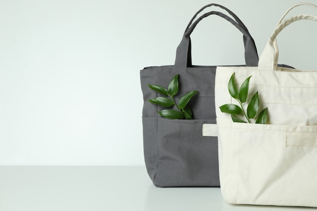 Stylish eco bags with twigs on white surface