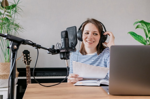 The stylish and educated caucasian woman records podcasts in a recording studio or in her home the